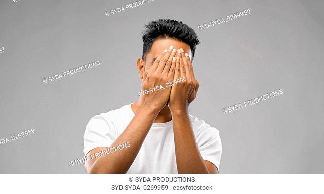 scared man covering his face with hands