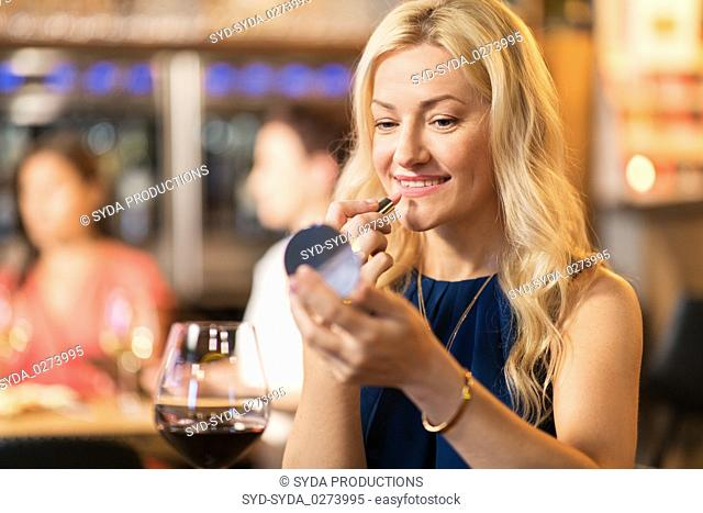 woman with lipstick applying make up at restaurant
