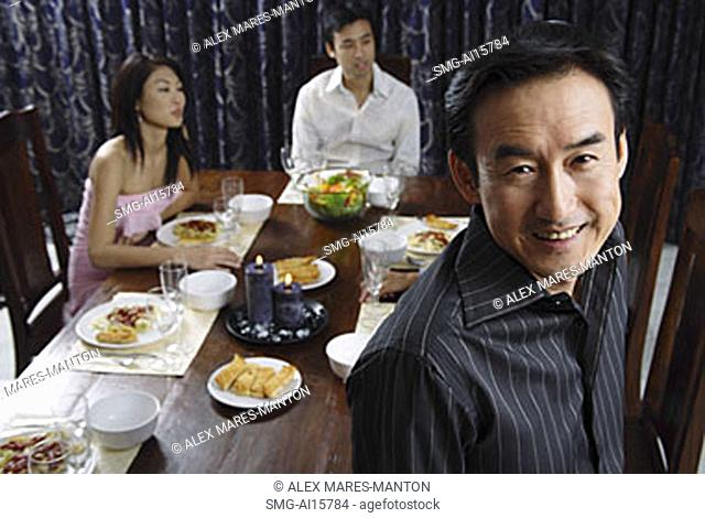 Man smiling at camera, people in the background sitting around table