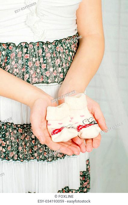 Baby socks in the hands of pregnant woman