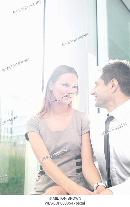 Businessman and businesswoman in love sitting in hotel lounge