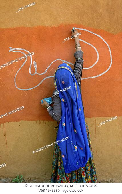 India, Rajasthan, Tonk region, Woman painting clay walls prior to Diwali festival