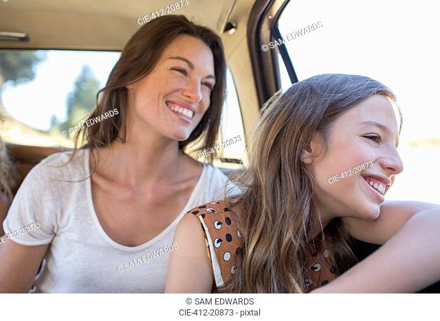 Sisters riding in car backseat together
