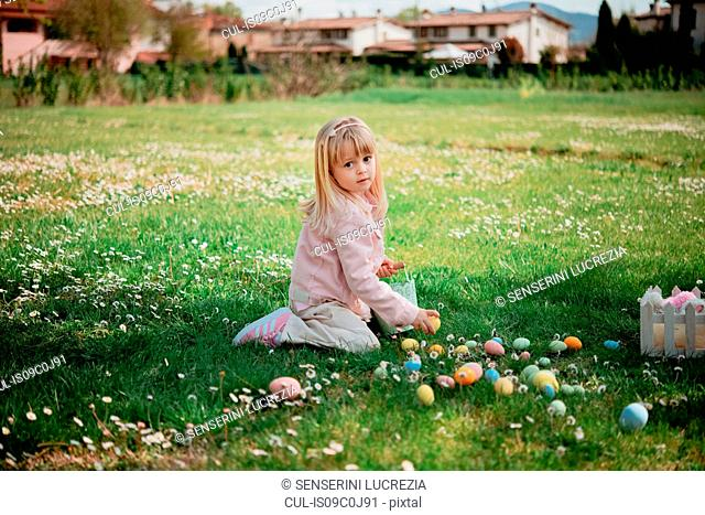 Cute girl sitting in field picking up easter eggs, portrait, Arezzo, Tuscany, Italy