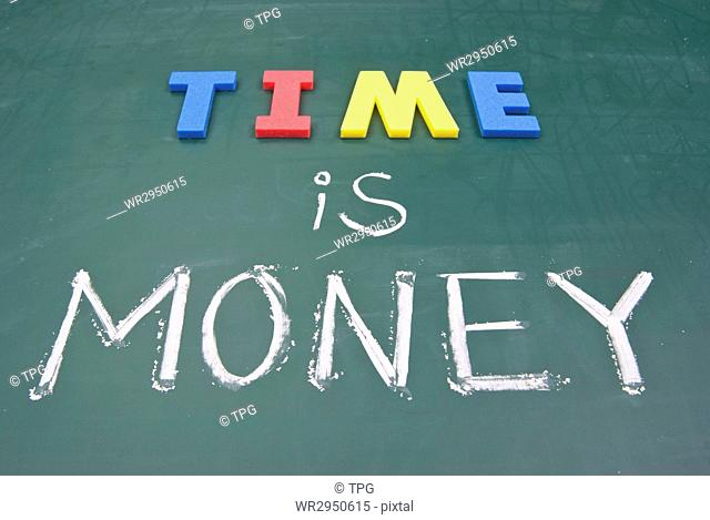 Time is money, business words on blackboard
