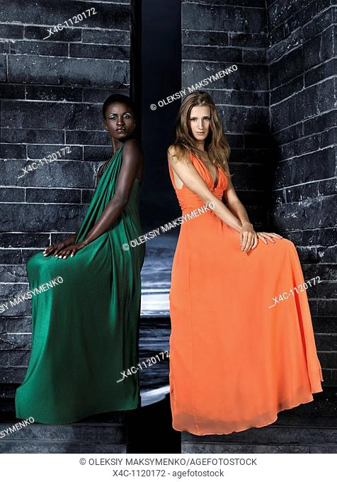 Two beautiful women in elegant dresses sitting on a black stone wall  High fashion
