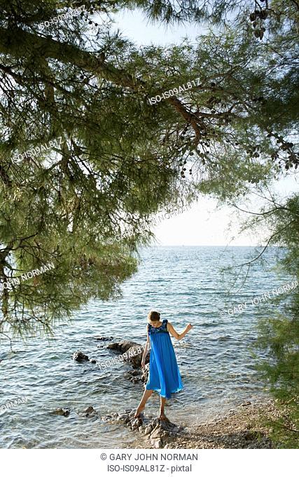 Young woman paddling in sea, Milna, Brac, Croatia