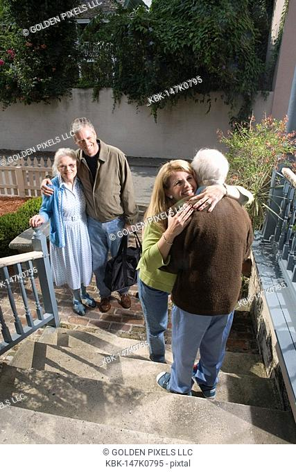 Woman cheerfully hugging senior man on steps while man and senior woman watch