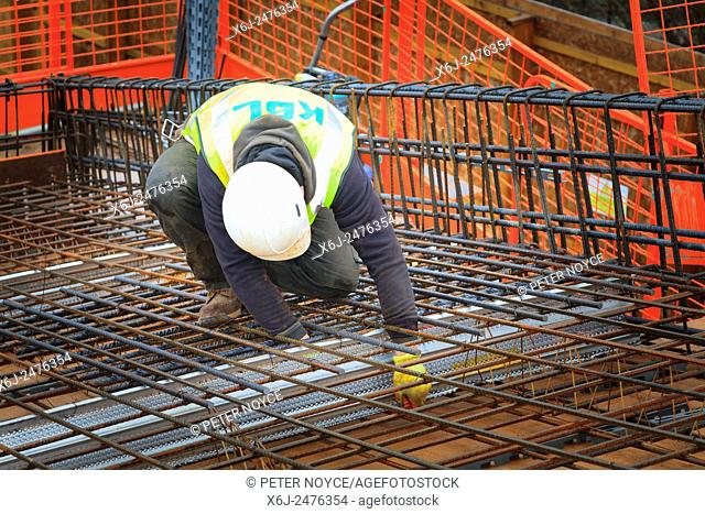 Construction worker tying up reinforcing bars prior to pouring of concrete on a commercial building roof