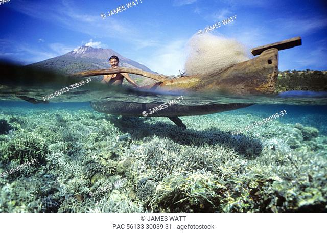 Indonesia, Pantar Island, over/under view of fisherman paddling along coral reef in canoe, volcano in background