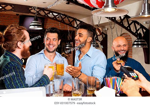 Man Group In Bar Drinking Beer, Mix Race Friends Meeting, Bearded Man Pay With Credit Card To Barmen Standing At Counter