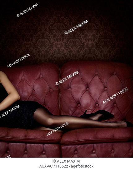 Closeup of sexy legs in black stocking of a woman lying on a luxurious pink red tufted couch wearing a short black dress and high heel shoes