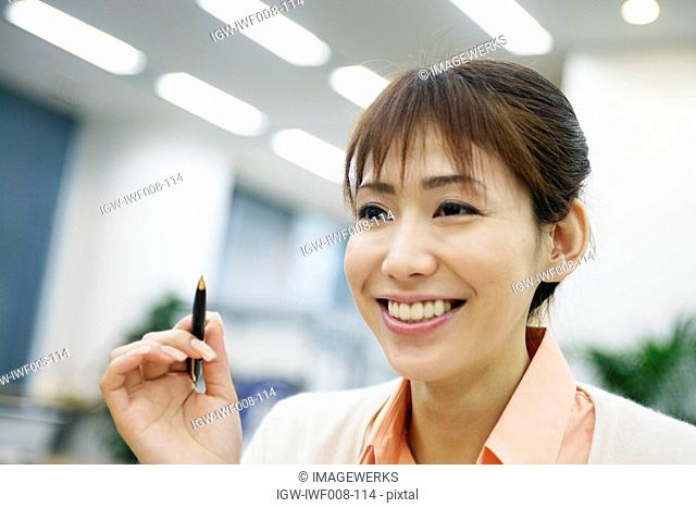 A woman holding a pen smiles at someone