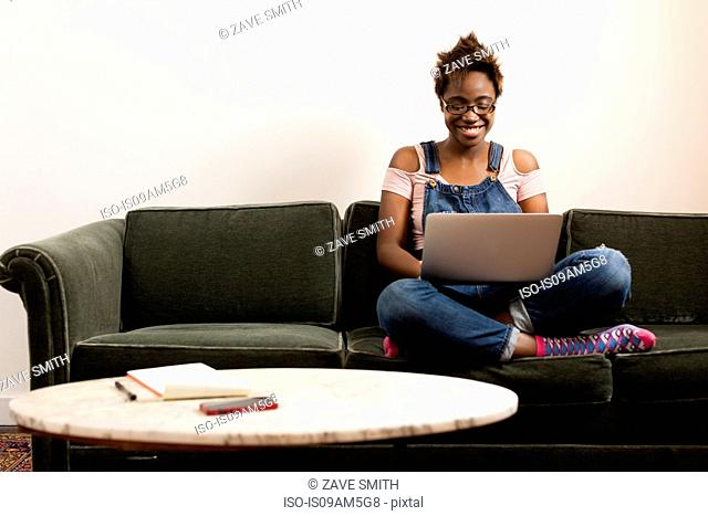 Woman working at laptop on sofa