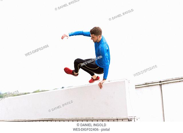 Young athlete crossing a wall