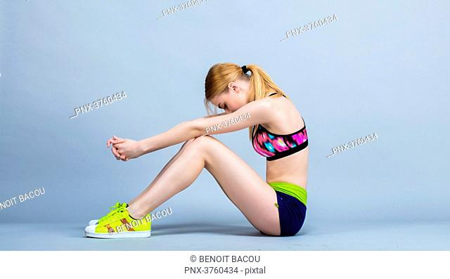Young woman sitting in keeping fitness, profile, focused, head down