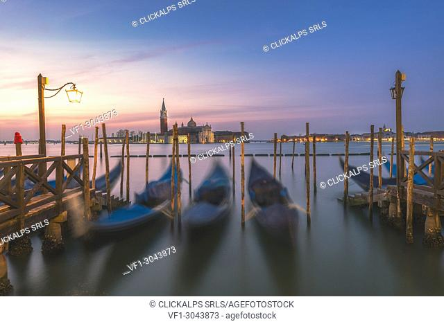 Gondolas tied up to wooden poles on the Canal Grande, in the background the monastery of San Giorgio Maggiore,Venice, Veneto, Italy