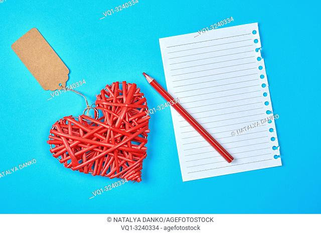 wooden wicker red heart and an empty white sheet of notepad, next to a pencil, blue background