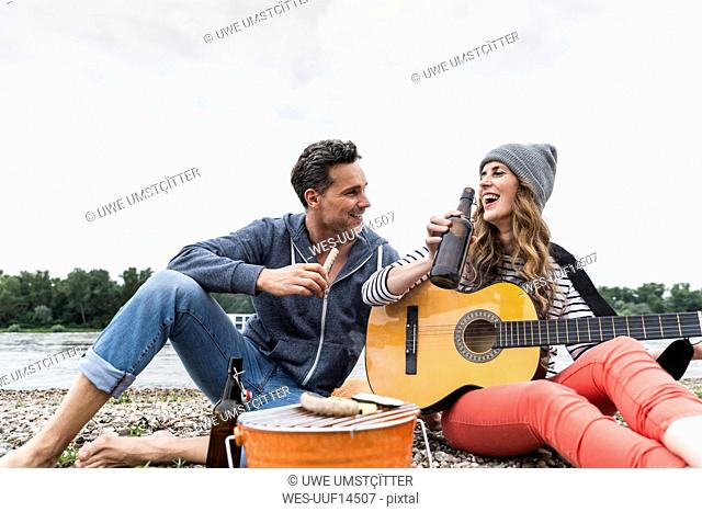 Happy couple with beer bottle, guitar and grill relaxing at the riverside