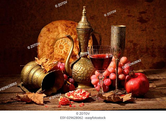 Red wine, juicy pomegranate, sweet grapes, flat cake and copper jug