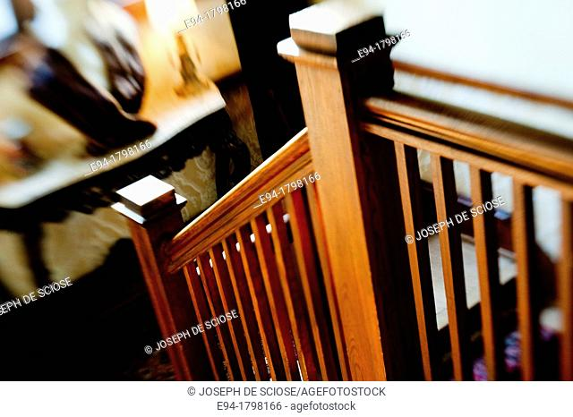 A narrow depth of field photo of a bannister railing on a staircase in a home