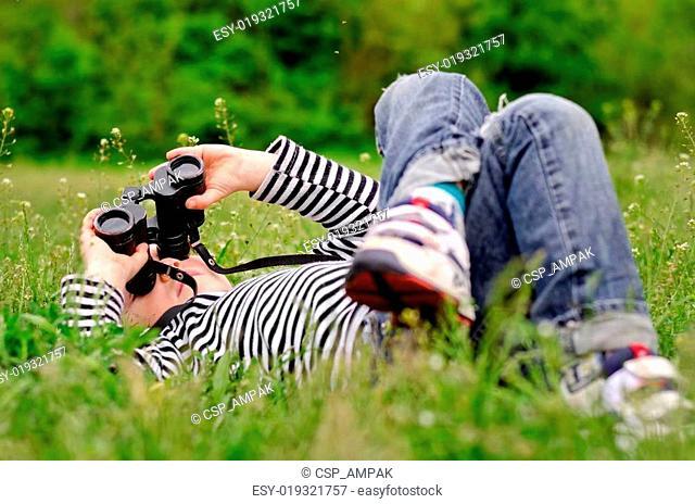 Little boy observing the sky through binoculars