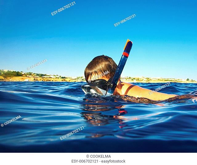 boy floats under water in the sea.