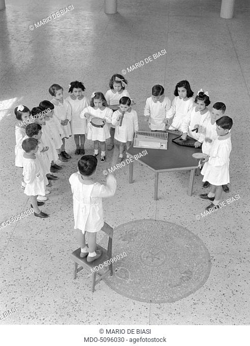 Children singing and playing music in a kindergarden. Milan, 1950s