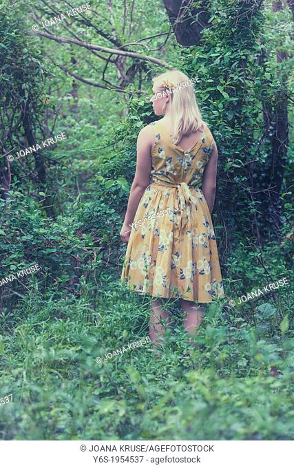 a blond girl with a yellow dress in the woods