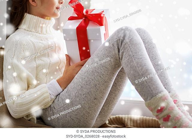 girl with christmas gift sitting on sill at home