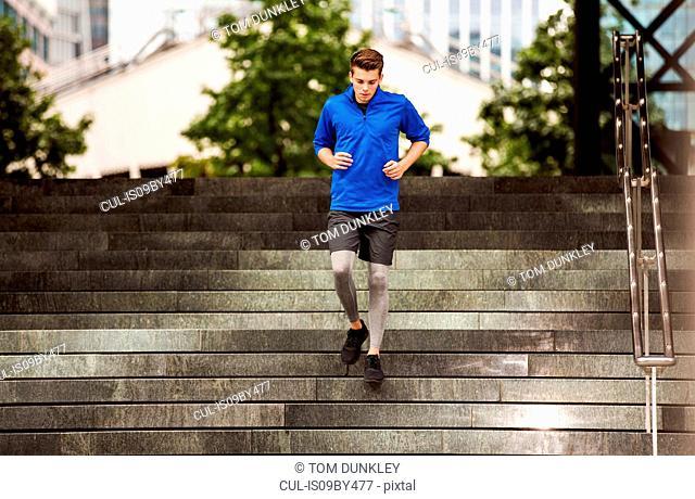Young runner jogging down steps, London, UK