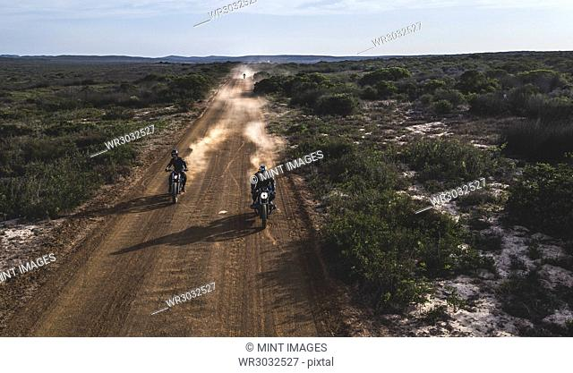Landscape with two men riding cafe racer motorcycles in circles on a dusty dirt road