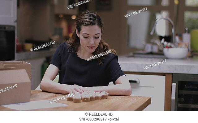 Young adult woman packing cupcakes at home in kitchen