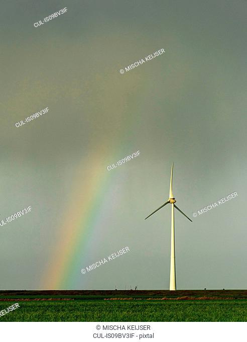 Field landscape with rainbow by turbine on wind farm in north Netherlands, near waddensea dyke