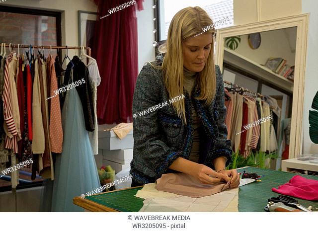 Fashion designer pinning on fabric in fashion studio