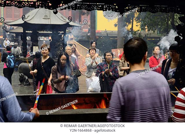 Crowds praying for blessings with incense sticks at the Ling Yin Buddhist temple Hangzhou China