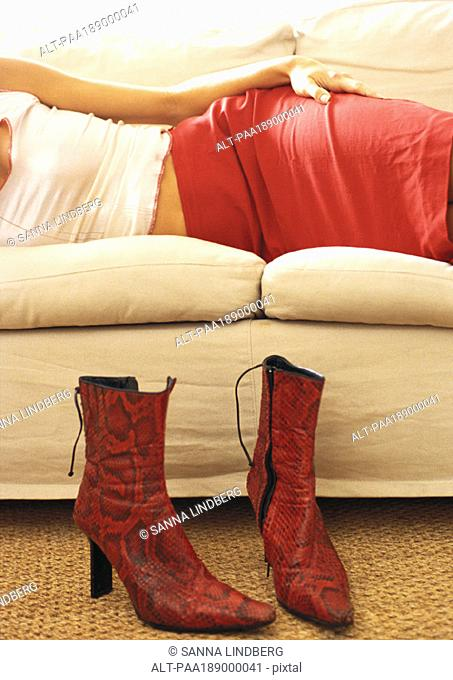 Mid section of woman lying on couch, boots on floor