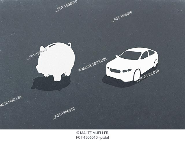 Piggy bank and car against gray background