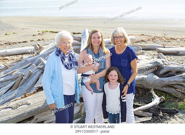 Four generations of women in a family posing on a beach; Fox Spit, Whidbey Island, Washington, United States of America