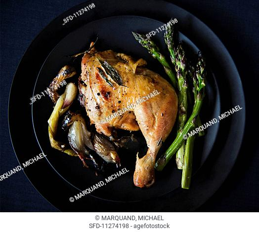 Roast chicken leg with grilled onions and asparagus
