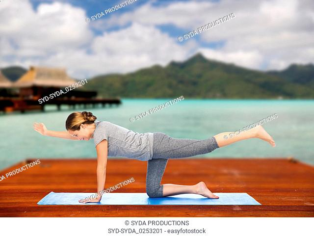 woman making yoga in balancing table pose outdoors