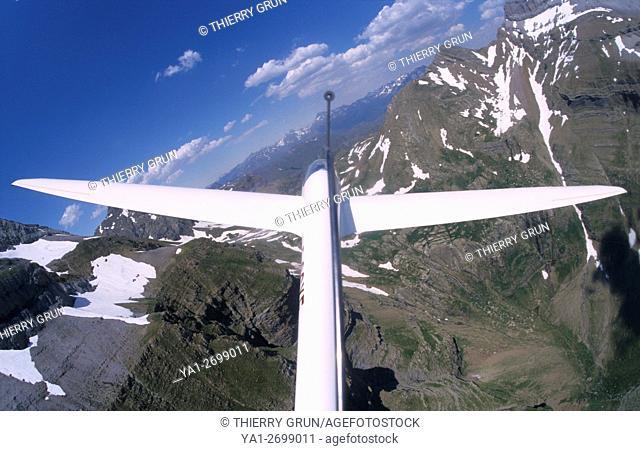 Glider plane Twin Astir flying in valley de Aurin between Pena Retona and Pena Collarada mountains, Aragon, Spain