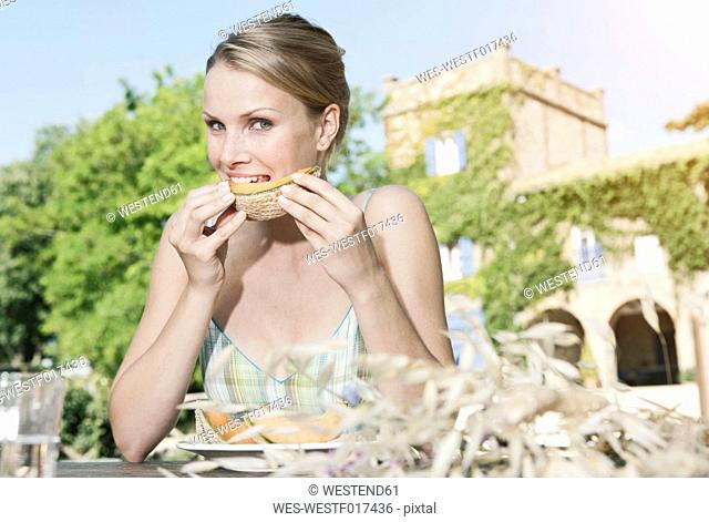Italy, Tuscany, Magliano, Young woman eating honey melon, portrait