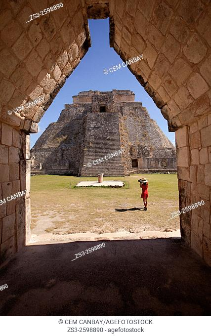Tourist taking photos of the the Pyramid of the Magician, Maya archeological site Uxmal, Yucatan, Mexico, Central America