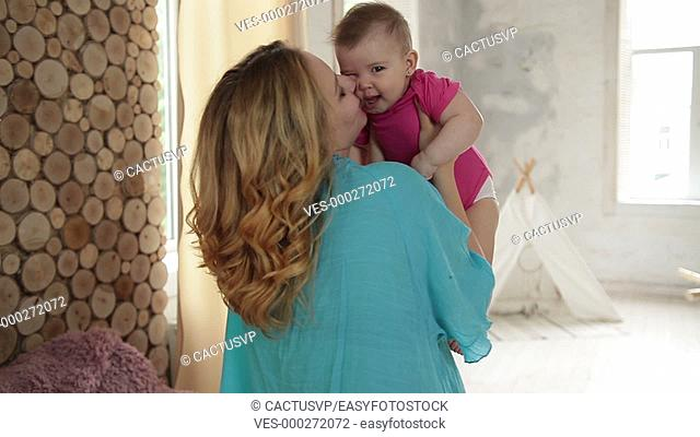 Caring mom kissing her adorable baby girl