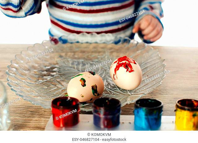 The child paints Easter eggs with paints,on white background