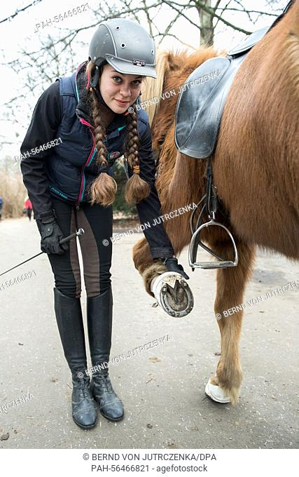 Greta Suechting, 16, shows the special nails in the hooves of her icelandic horse Hera on an ice rink in Berlin, Germany, 6 March 2015