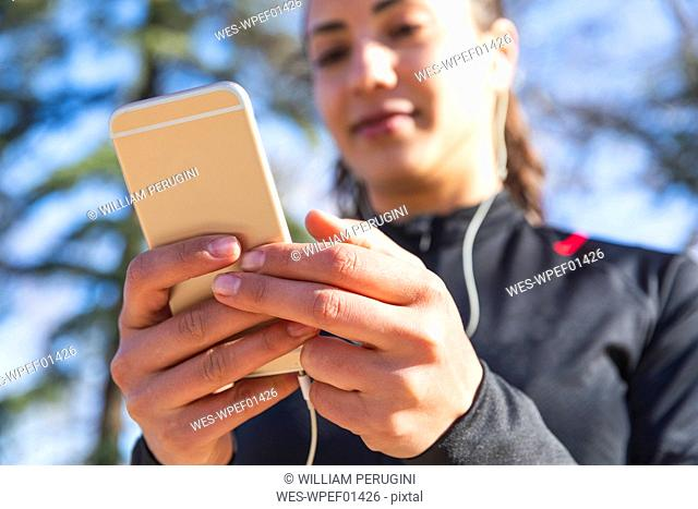 Close-up of young woman training and checking her smartphone
