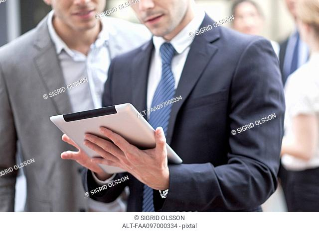 Businessman showing colleague digital tablet
