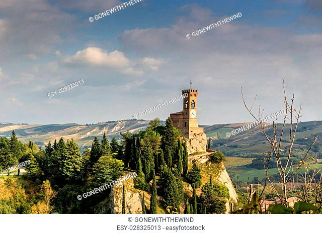 The medieval clock tower surrounded by cypress and other trees, viewed from the Rock of Brisighella in Emilia Romagna, Italy